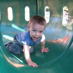 child crawling through a plastic toy tunnel